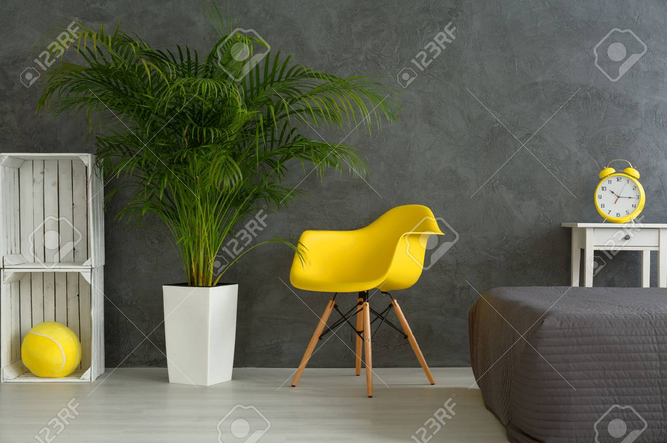 Modern Designed Bedroom With Grey Walls. Yellow Chair Next To Green Plant  And White Shelf