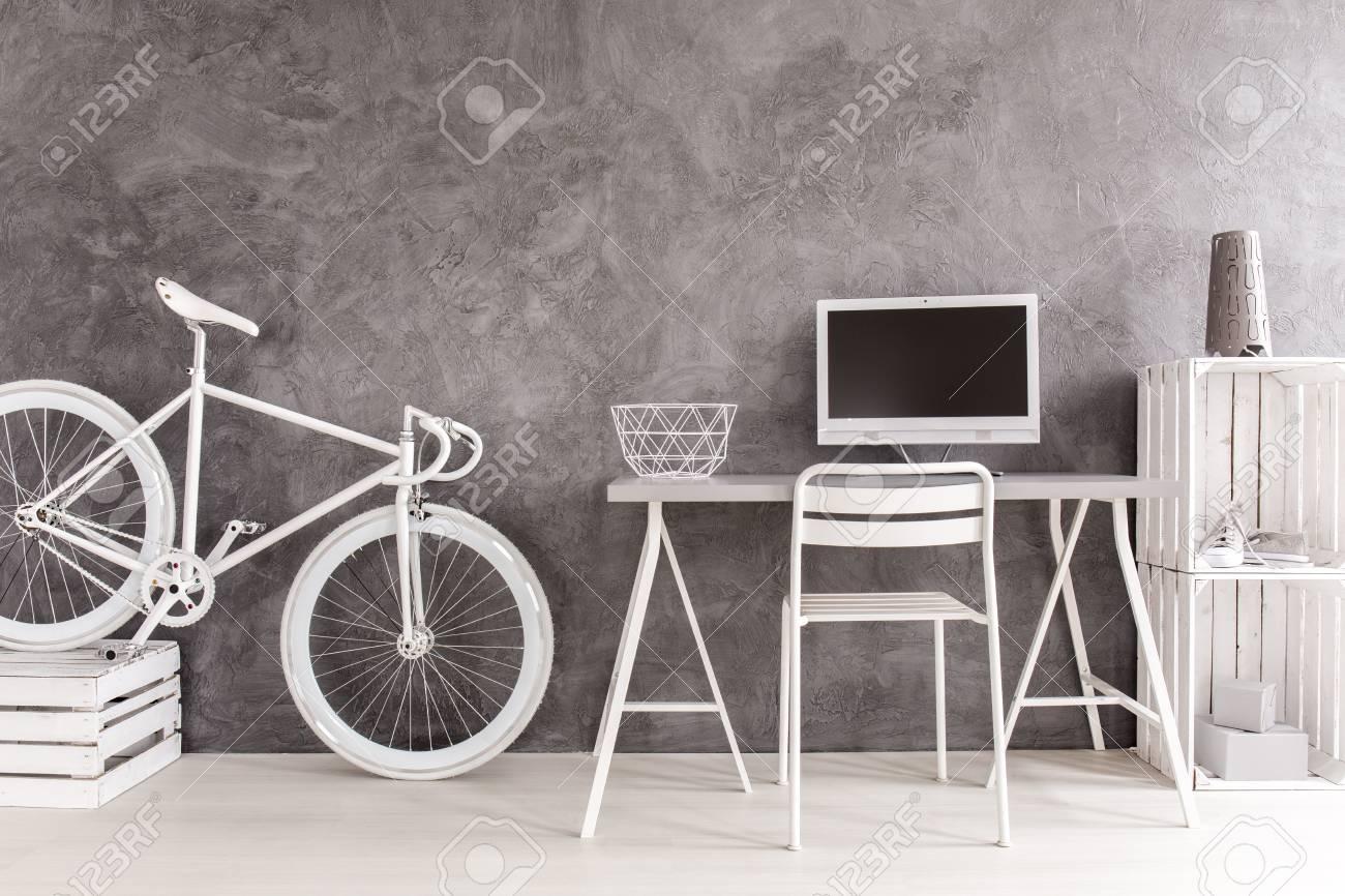 Bureau à domicile moderne avec des murs gris et un plancher en