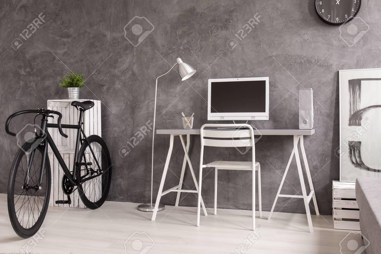 Gris salon moderne avec bureau blanc et étagère. À côté de lui en