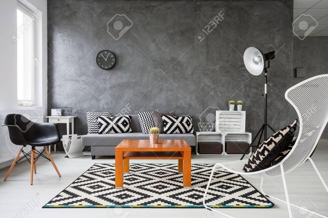 Salon avec murs gris et parquet en bois blanc. Décorations en noir et blanc  avec une table basse orange au milieu de la pièce