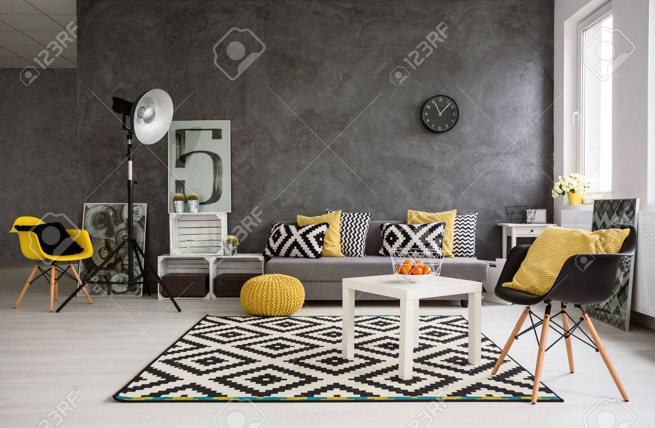 Stylish spacious living room with grey walls and black, white..