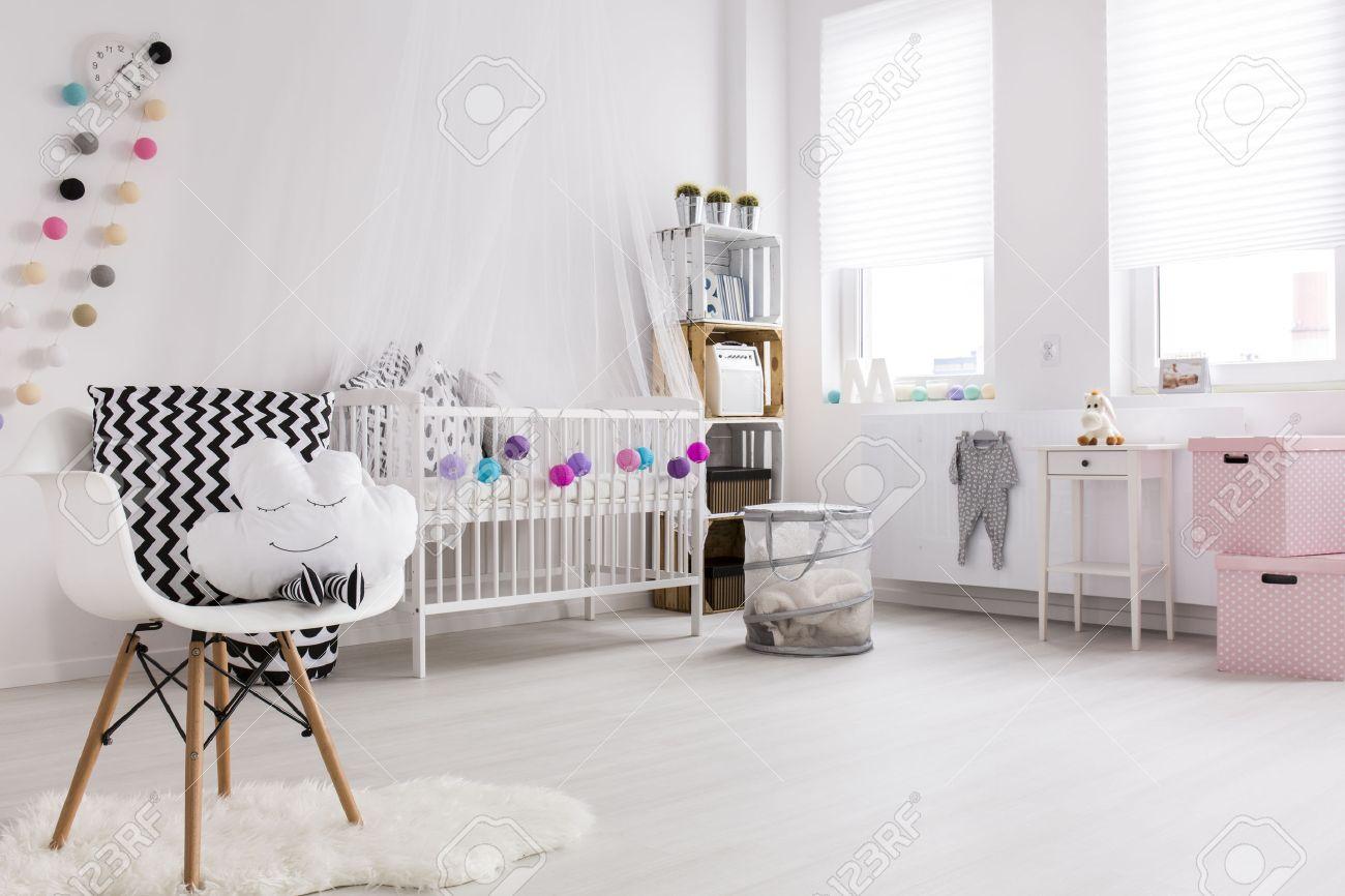 Spacieuse chambre blanche et rose avec plancher en bois pour le petit bébé.  Berceau blanc avec décorations et auvent au mur