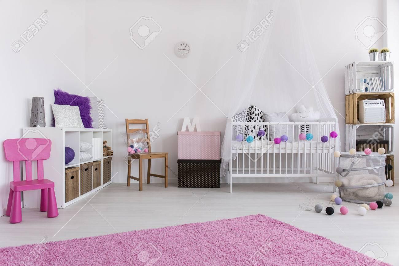 Rose mignon et chambre blanche conçue pour petite fille. Par le berceau de  la paroi et l\'étagère. Sur le tapis plancher rose