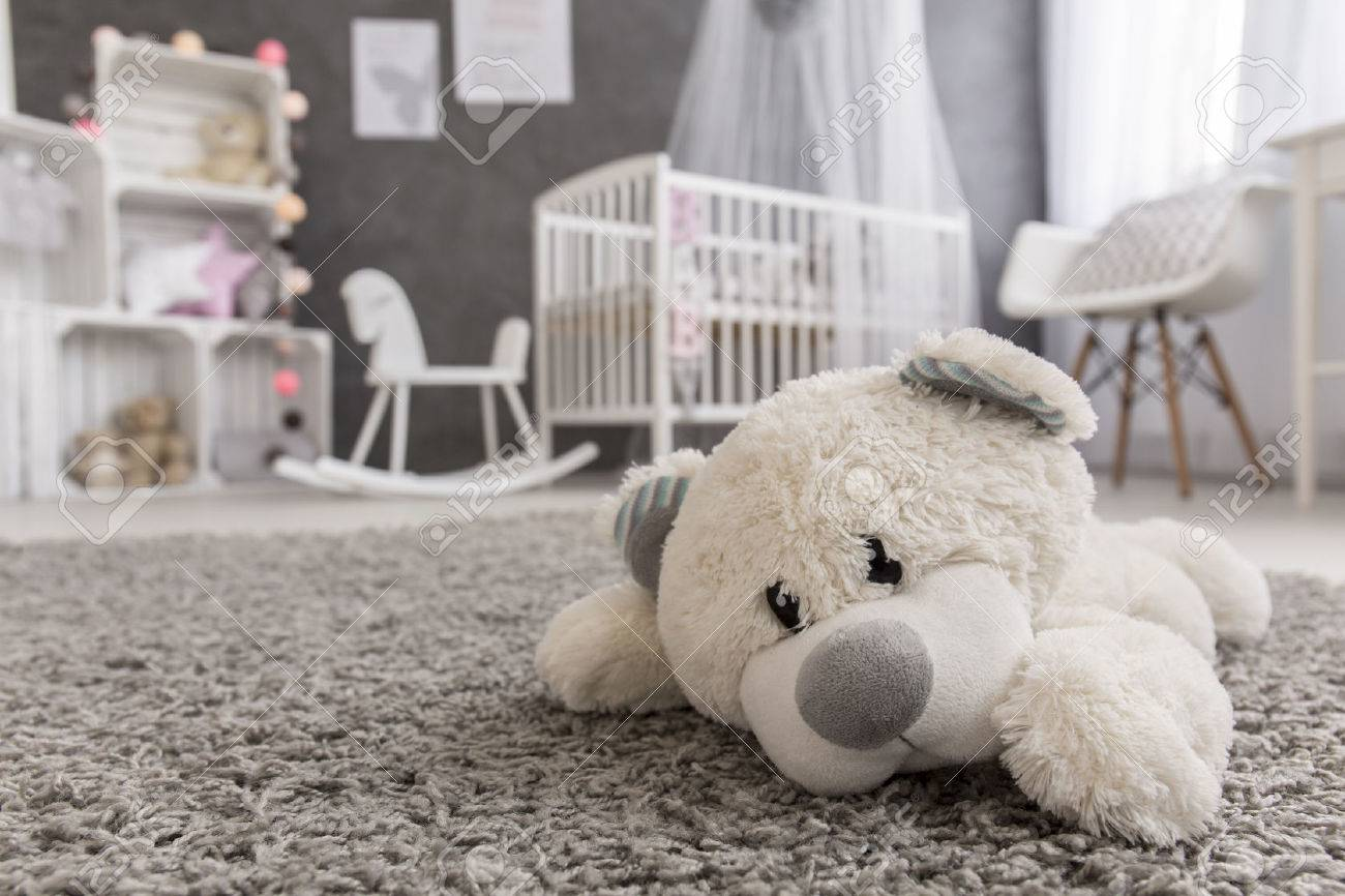 Shot of a teddy bear laying on a carpet in a cozy baby girl room - 57978918