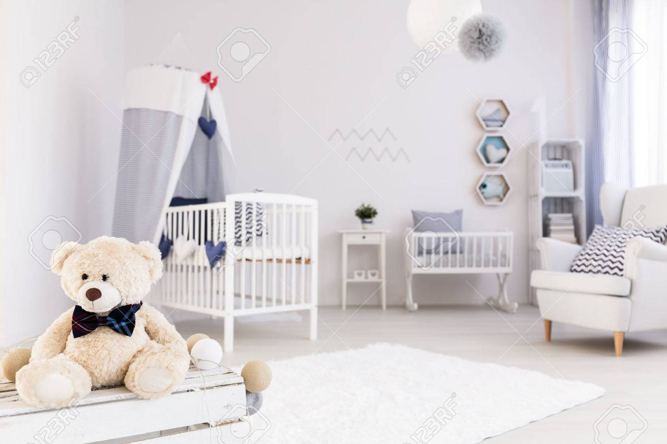 Light And Spacious Baby Room With White Furniture, Teddy Bear In The  Foreground Stock Photo