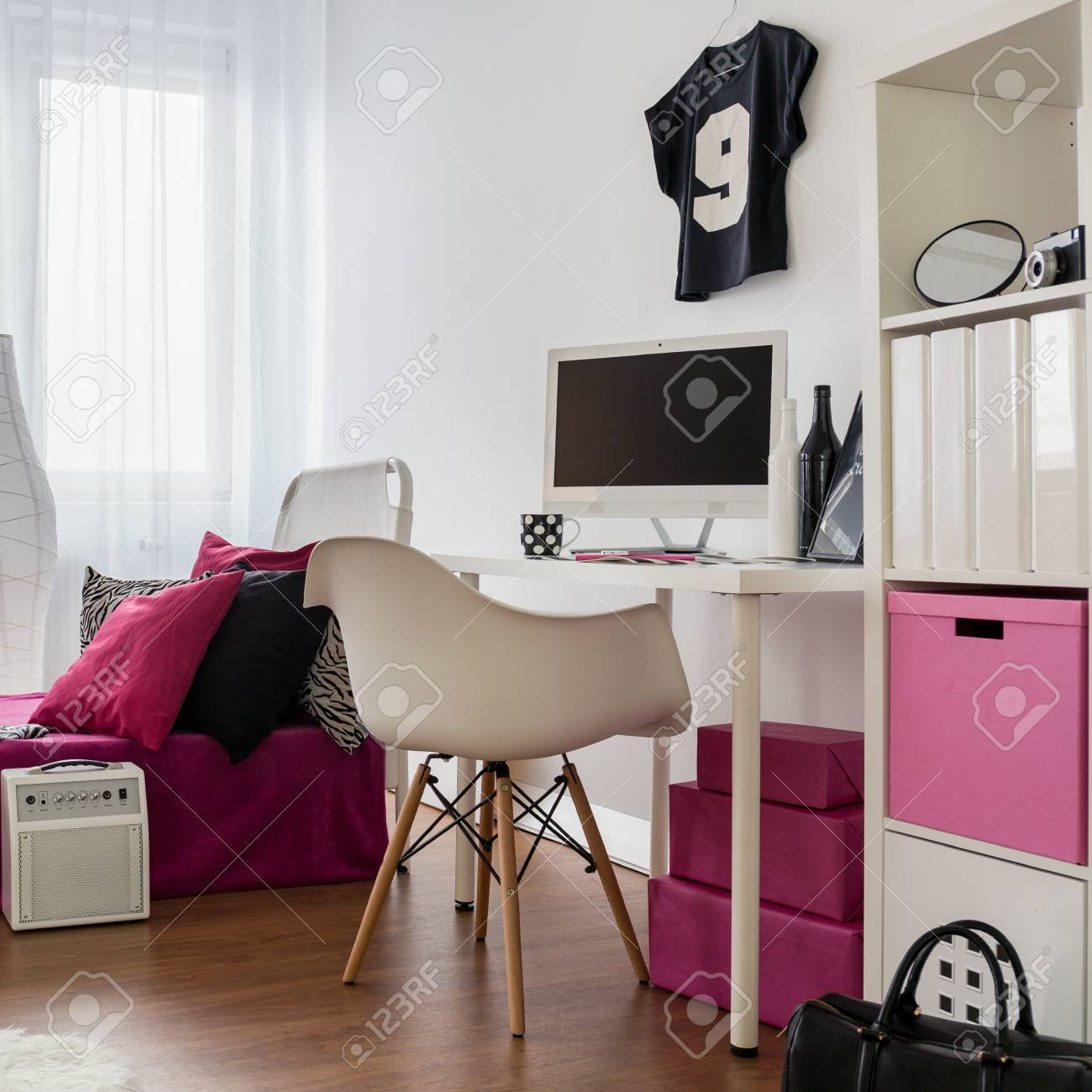 Bedroom and study room combined. Girly interior in black, pink..