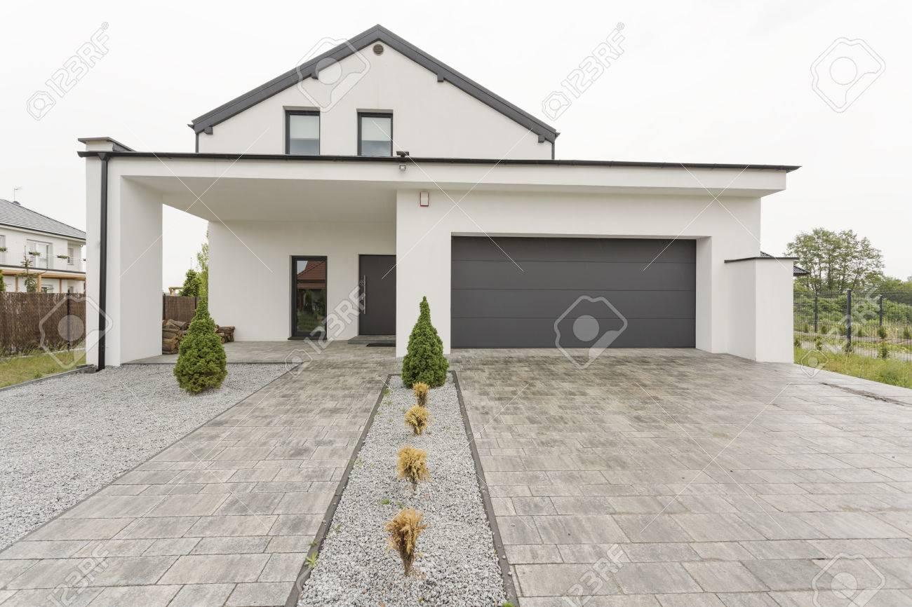 Vue de l\'extérieur d\'une maison moderne, blanc, d\'un garage et pierre allée