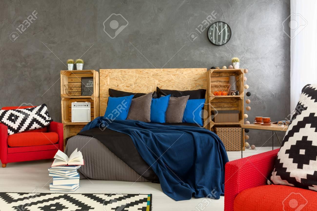 Standard Bild Stilvolle Schlafzimmer Mit Grauen Wänden Und Roten Sessel Mit  Wenig Durcheinander Auf Dem Bett