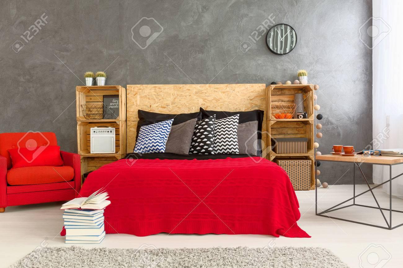 Moderne Chambre Conçue Avec Lit Rouge Et Un Fauteuil Sur Le Mur De ...
