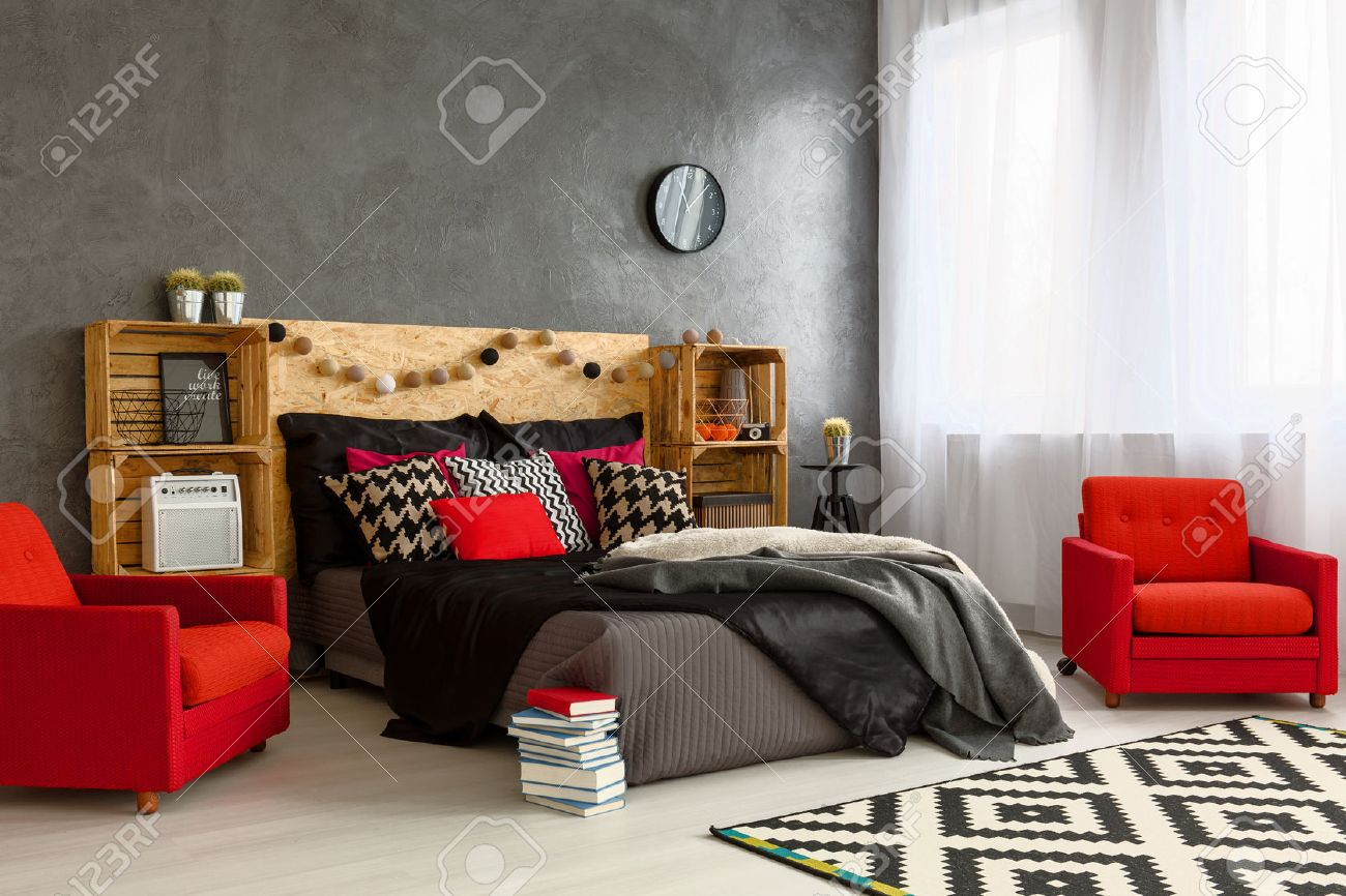 Spacious New Bedroom Decorated With Style. Cozy Double Bed With Wooden  Headboard Red Armchairs And