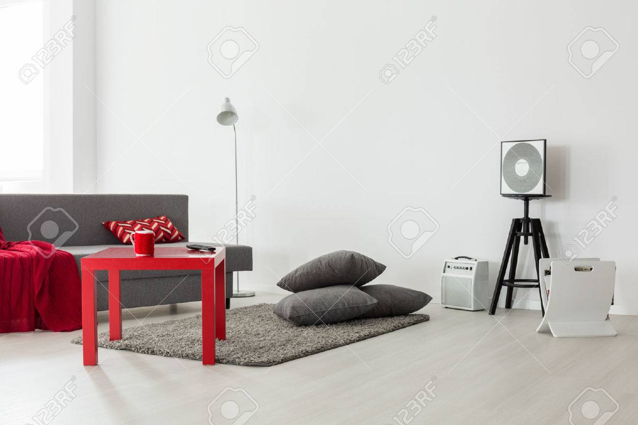 Minimalist Interior Of A Bright Living Room With Grey Sofa Red Coffee Table And