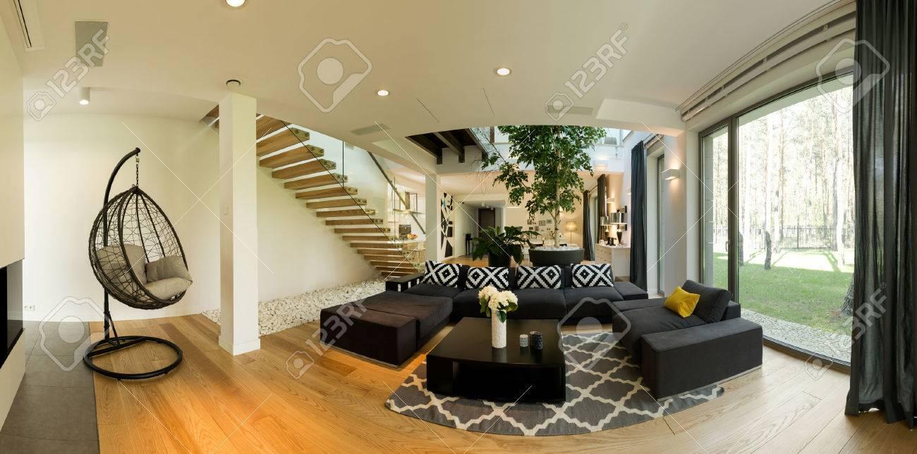 Très spacieux rez-de-chaussée d\'une maison de design contemporain, avec un  grand salon noir et une chaise suspendue