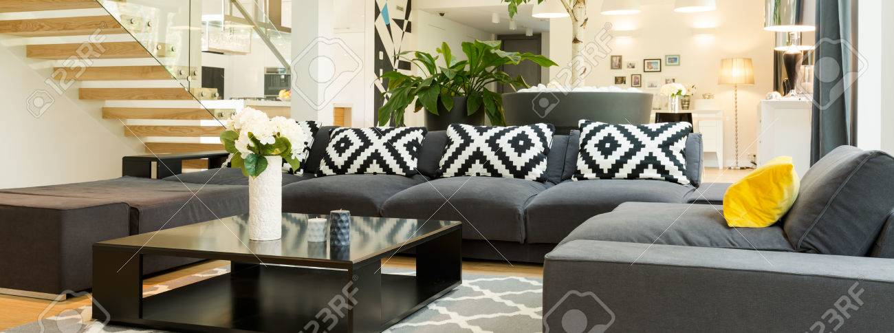 Attirant Stock Photo   Very Large And Stylish Black Corner Sofa With A Designer  Coffee Table, Next To Stairs With Glass Railing