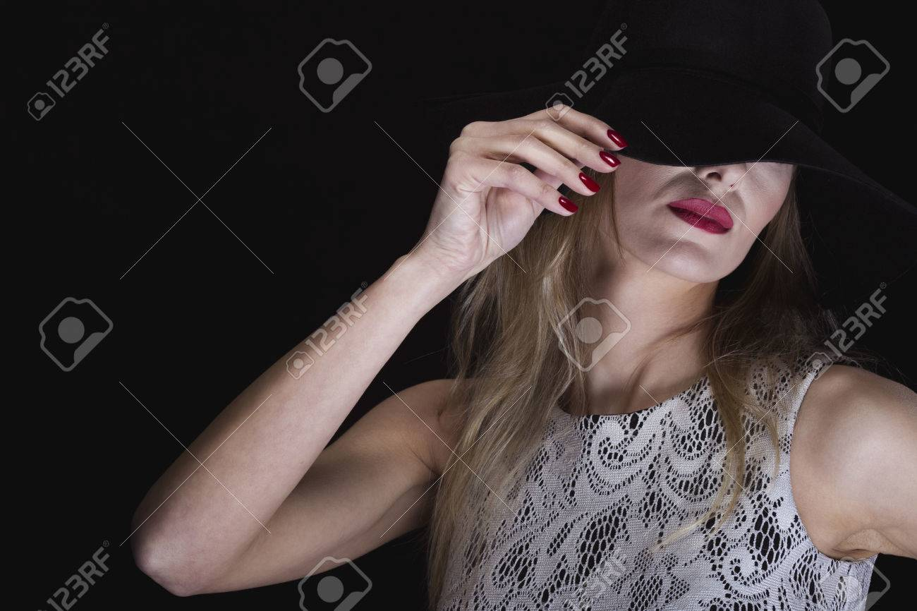 5ae8e7f2257 Shot of a beautiful woman in classic makeup wearing a black hat partly covering  her face