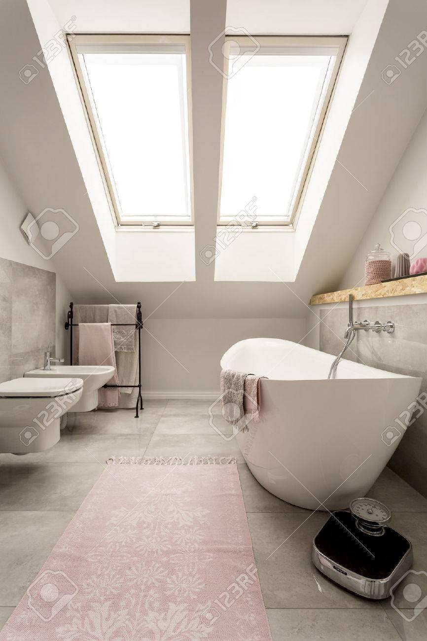 Nouvelle salle de bains mansardée design avec grande fenêtre, baignoire,  toilettes et bidet