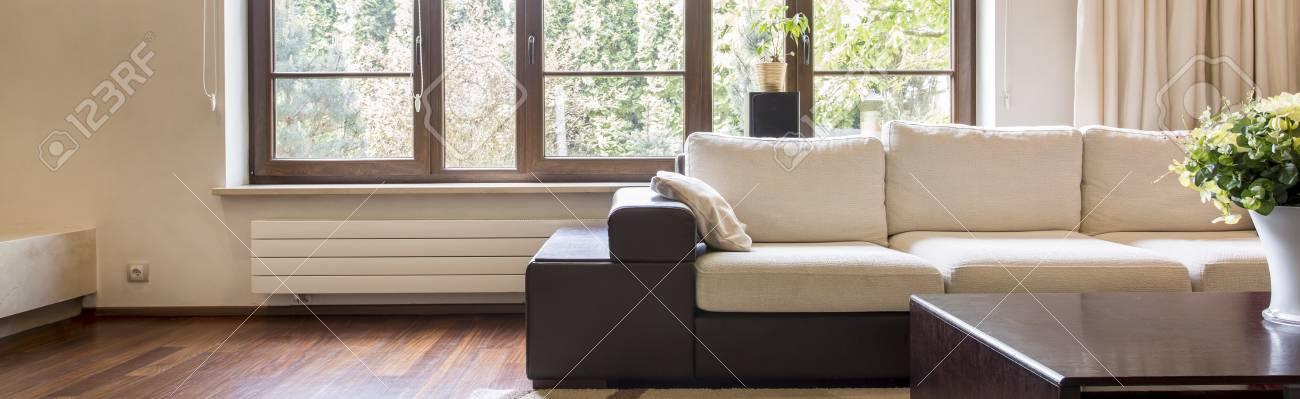 Chaleureux Salon Beige Et Marron Avec De Grandes Fenetres Un Canape Confortable Et Une Petite Table
