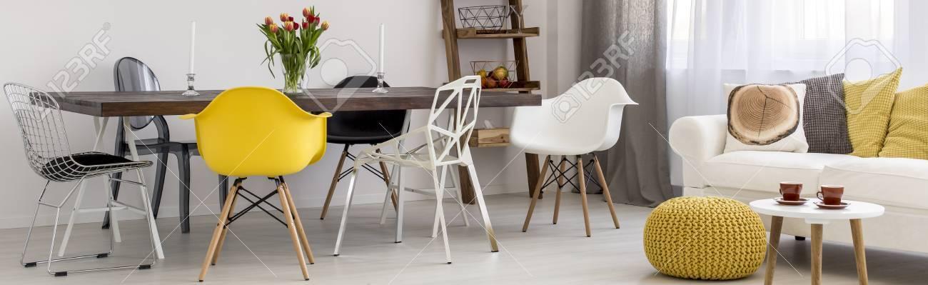 Soggiorno con tavolo in legno, sedie design e divano
