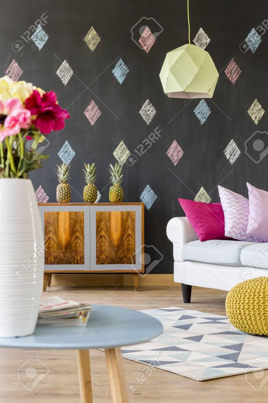 Cette chambre moderne avec tableau noir, commode exotique, canapé, lampe de  plafond, modèle de tapis et une petite table