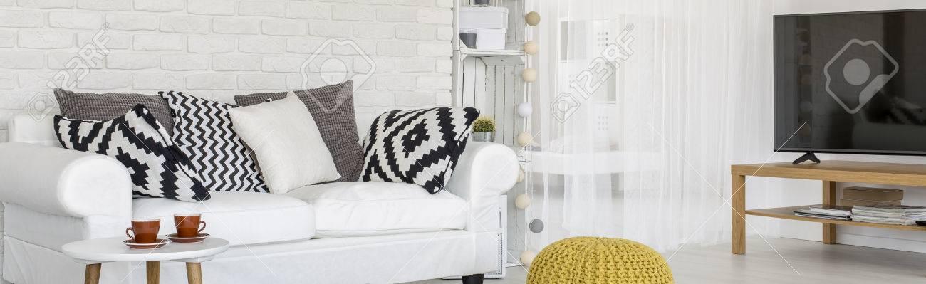Standard Bild   Wohnzimmer Mit Weißen Mauer. Im Zimmer Sind Couch, Fernseher  Platziert, Hocker Und Couchtisch