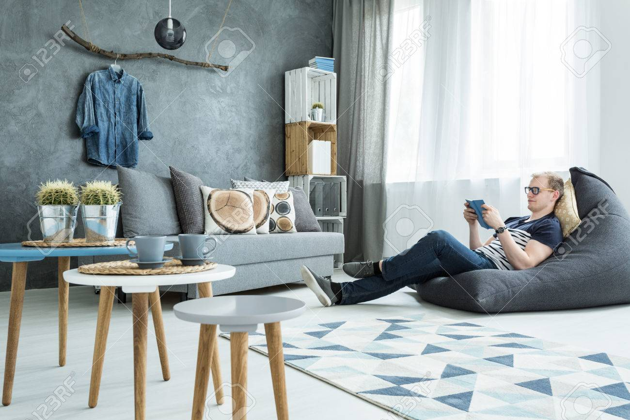 Modern Style Interior In Grey With Sofa, Stylish Futniture, Man Sitting On  A Bean