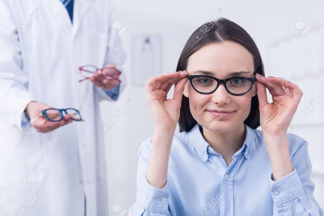 La Mujer Joven Sonriente Pequeña Elegir Las Gafas Perfectas. En El ...