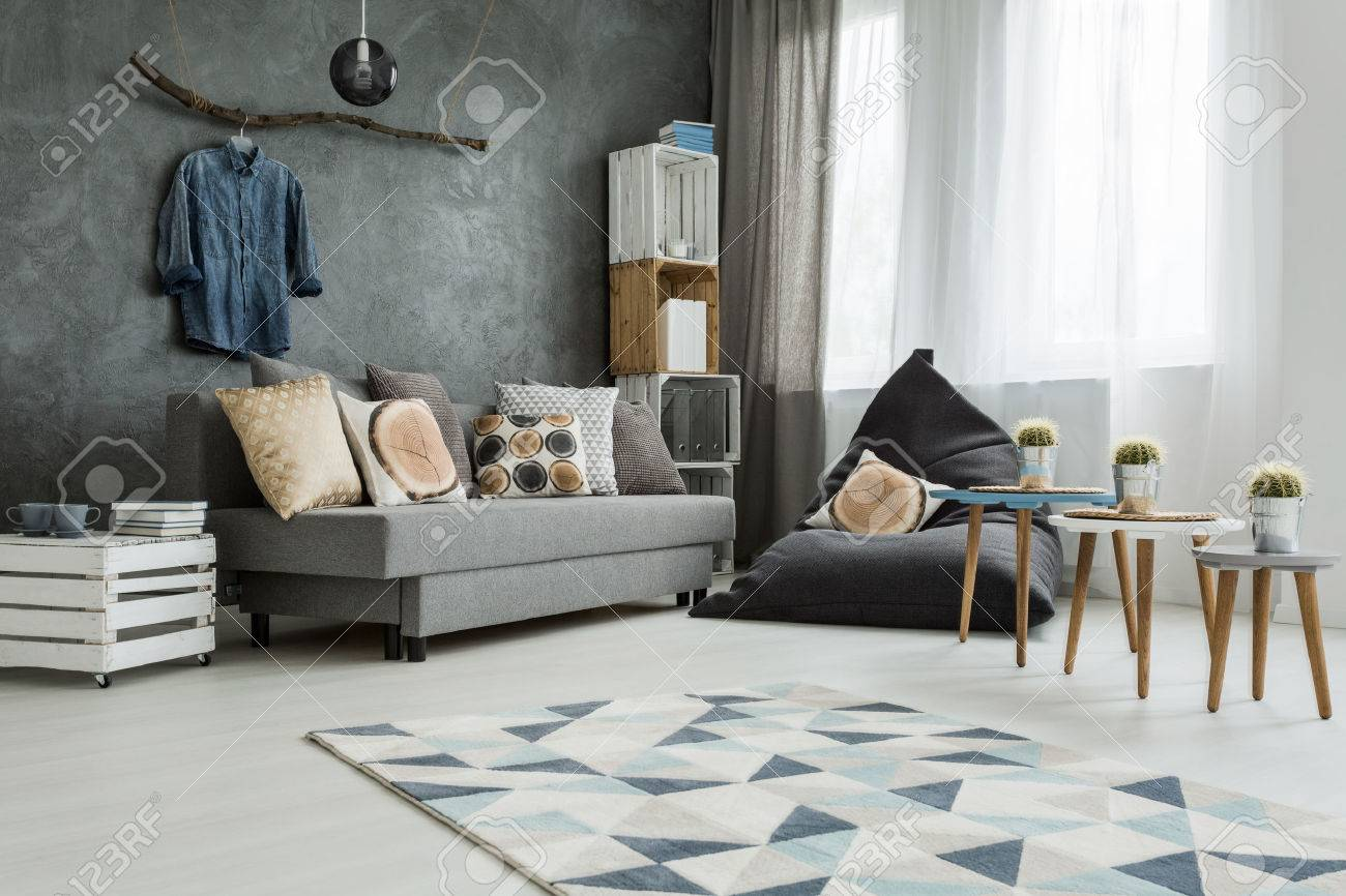new apartment interior in grey with sofa, modern pouf, small