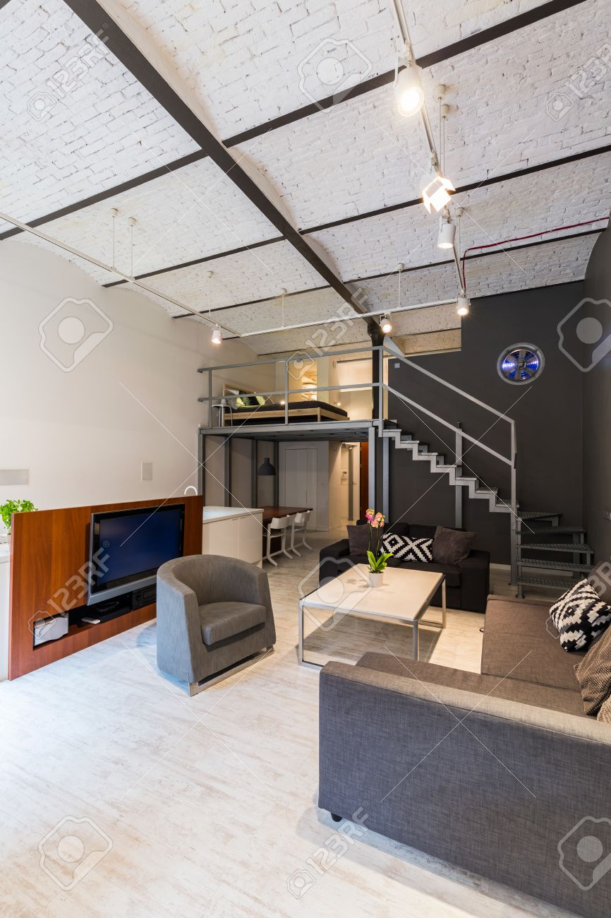 photo modern apartment with stylish living room furniture set television stairs mezzanine and brick roof