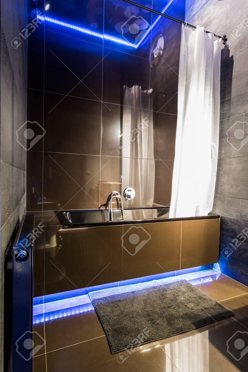 New Bathroom With Black Tiling, Bathtub And Blue Led Lighting Stock ...