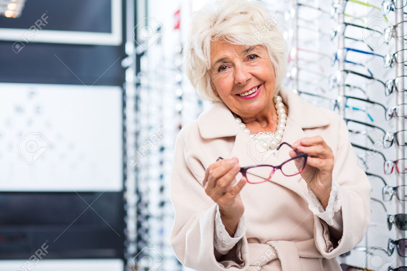 Elegant Senior Lady At The Optician\'s, Trying On One Of The Many ...