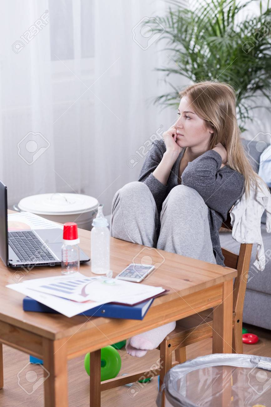 Young Mother Working At A Computer In A Living Room With Messy ...