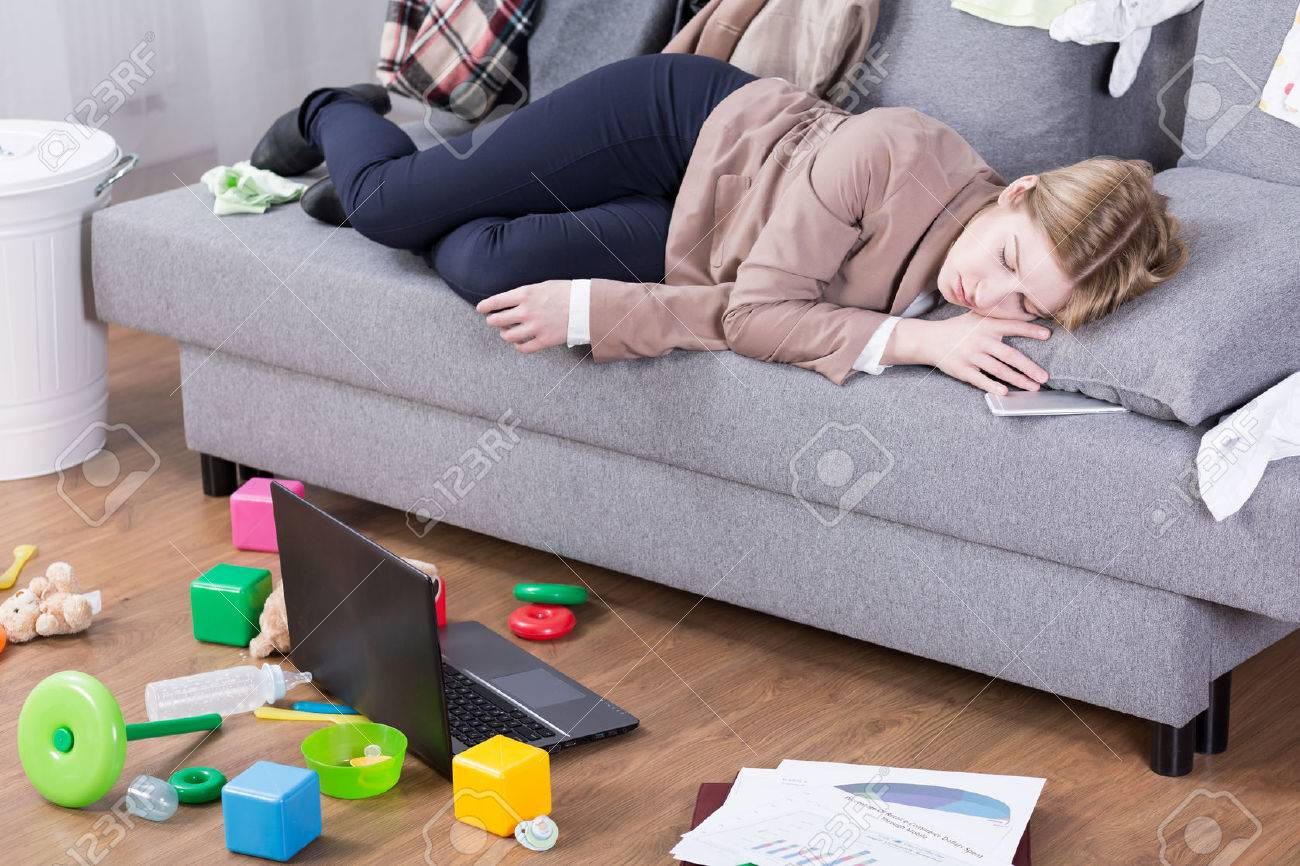 Young mother sleeping in her office clothes on a sofa in a messy living room Standard-Bild - 60367466