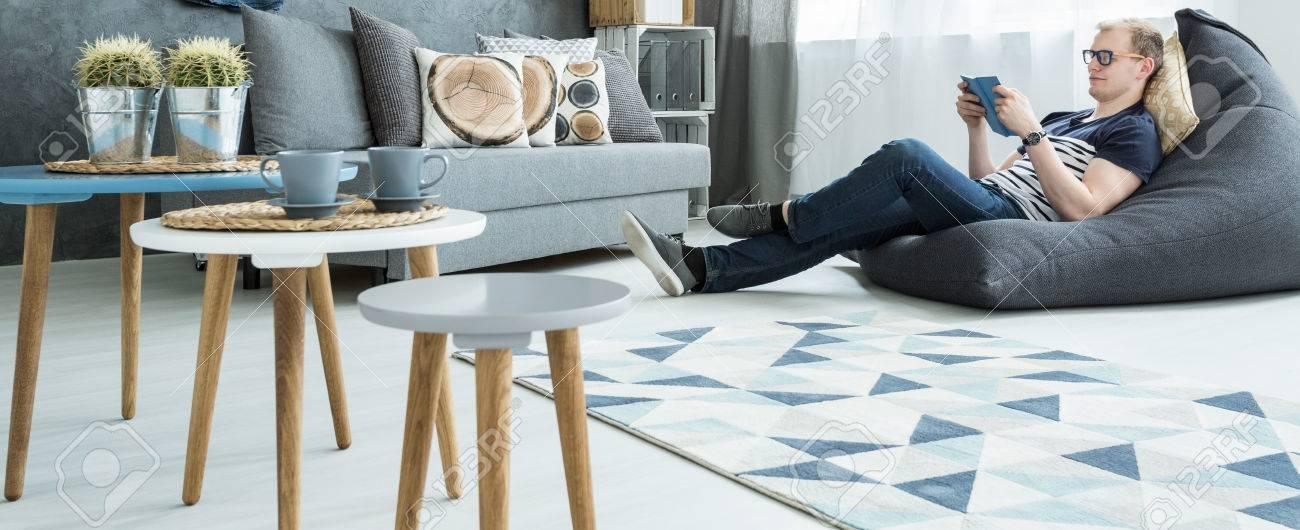 Panorama Eines Modernen Wohnung In Grau Und Weiß, Wo Ein Junger Mann, Ein  Buch