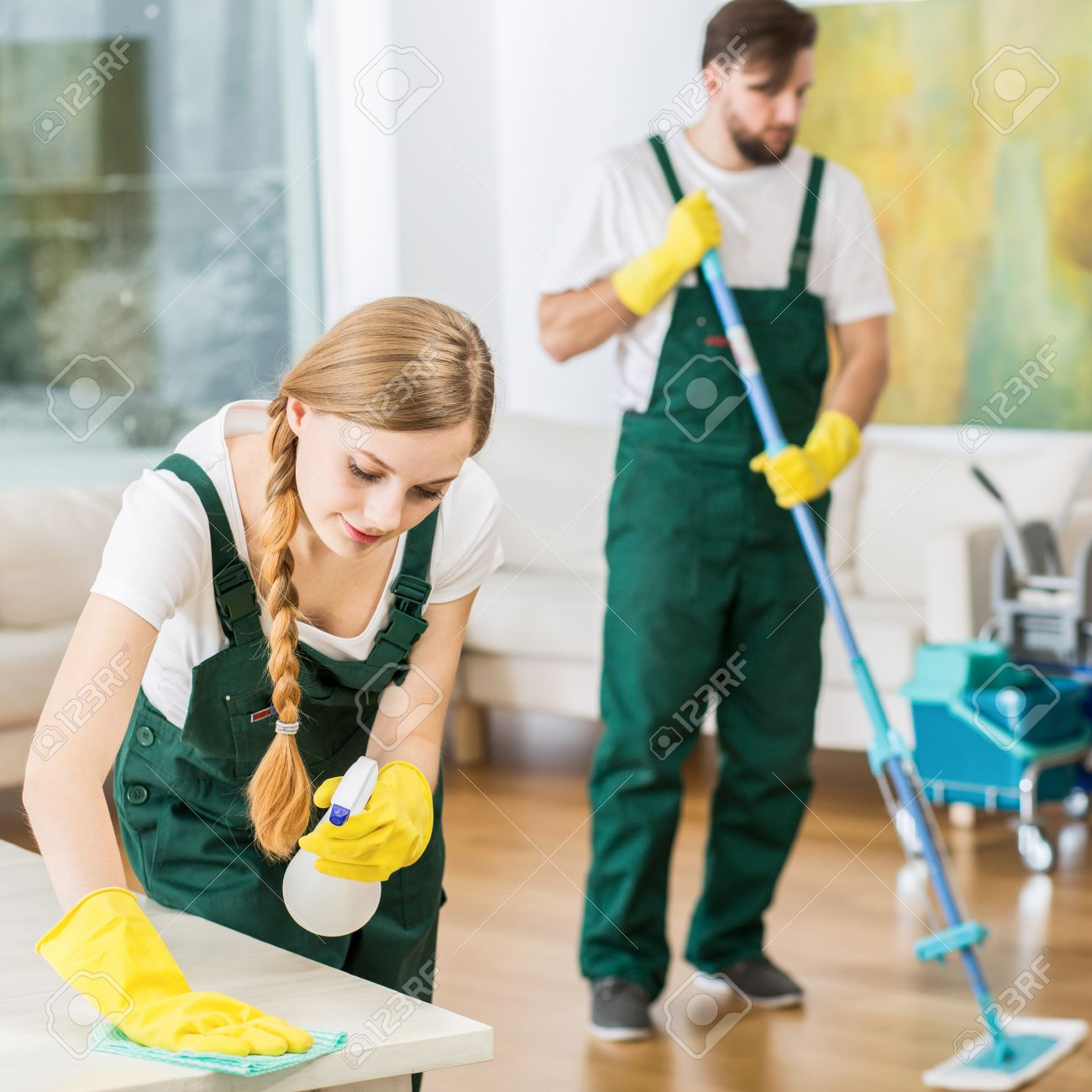 Young Professional Cleaners Cleaning Accurate Spacious Apartment. Man  Mopping The Floor And Girl Polishing The