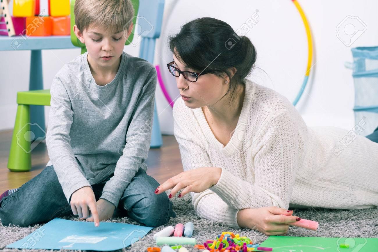 Boy and female pedagogue working with commitment on the carpet Standard-Bild - 60510948