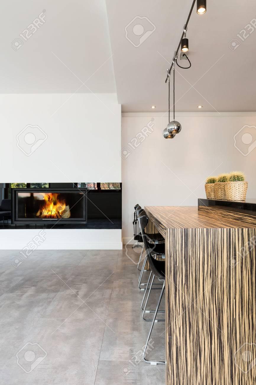 Salon très moderne dans un style minimaliste, avec cheminée et un bar à  manger avec chaises de bar