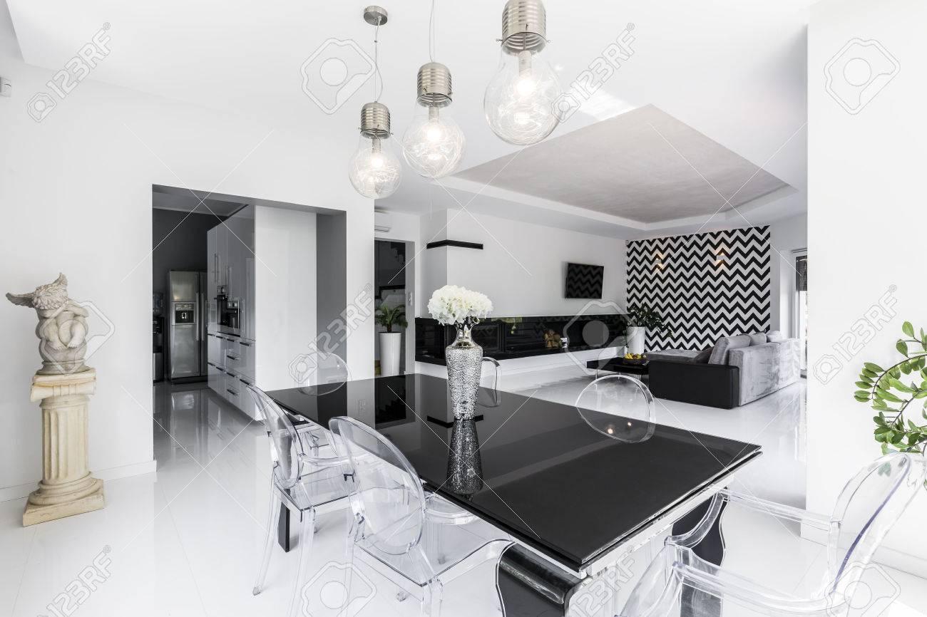 Salle A Manger Gris Blanc Noir luxueuse salle à manger en noir et blanc avec table noire et chaises  fantômes, salon ouvert en arrière-plan