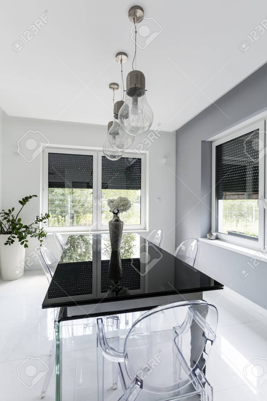 New style white dining room with black glass table and ghost..
