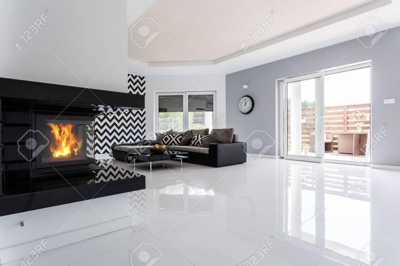Blanc et spacieux salon moderne avec cheminée et grand canapé