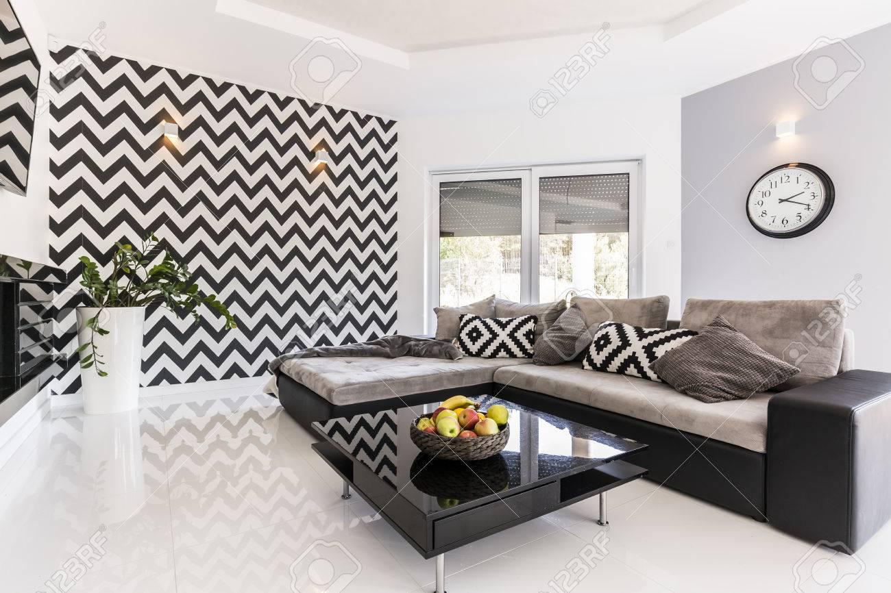 Nouveau style salon spacieux avec un grand canapé, noir petite table et le  papier peint de motif