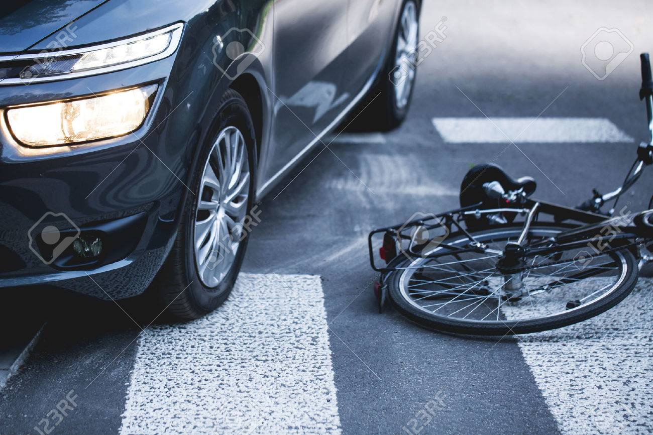 Car standing on the pedestrian path with the downed bicycle Standard-Bild - 60983135