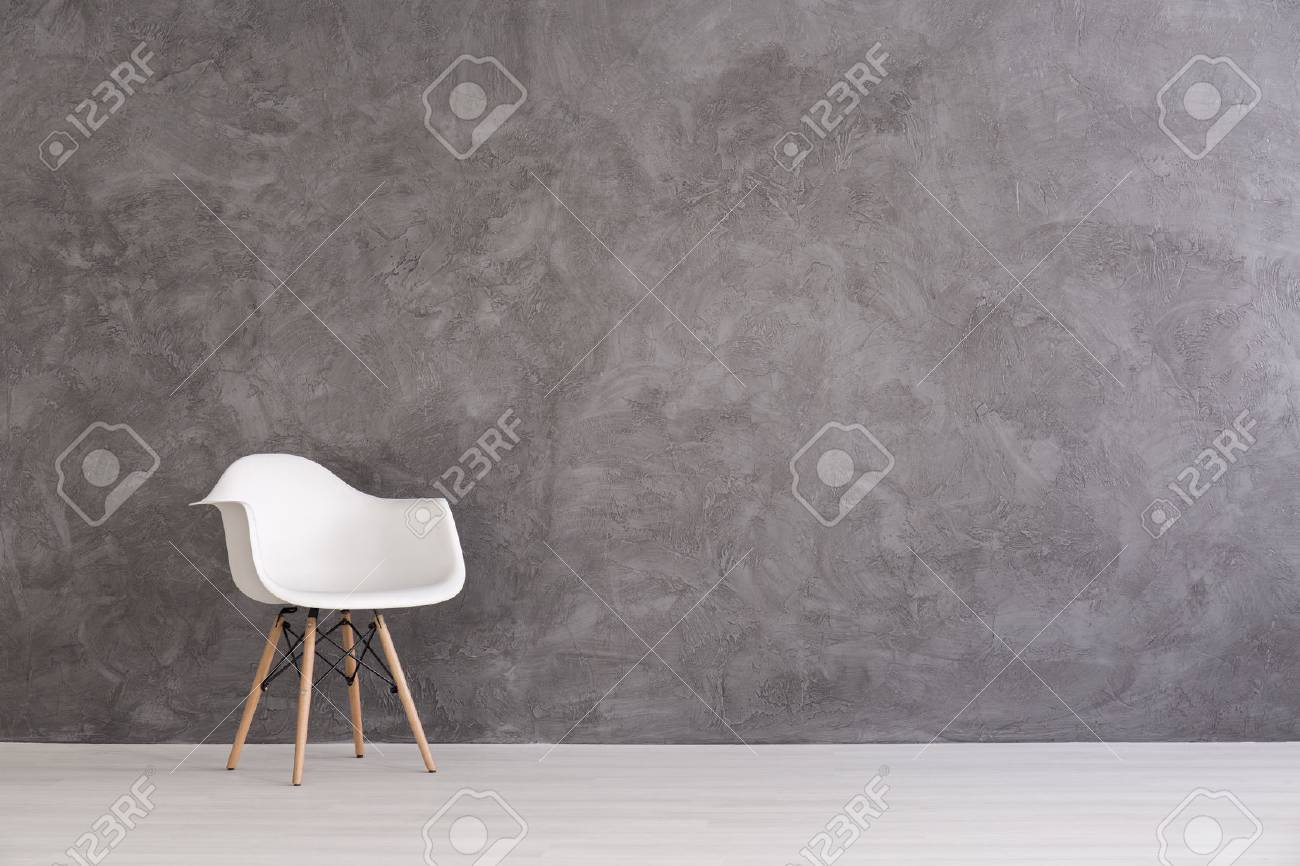 White plastic chair on a background of a gray concrete wall - 60771994