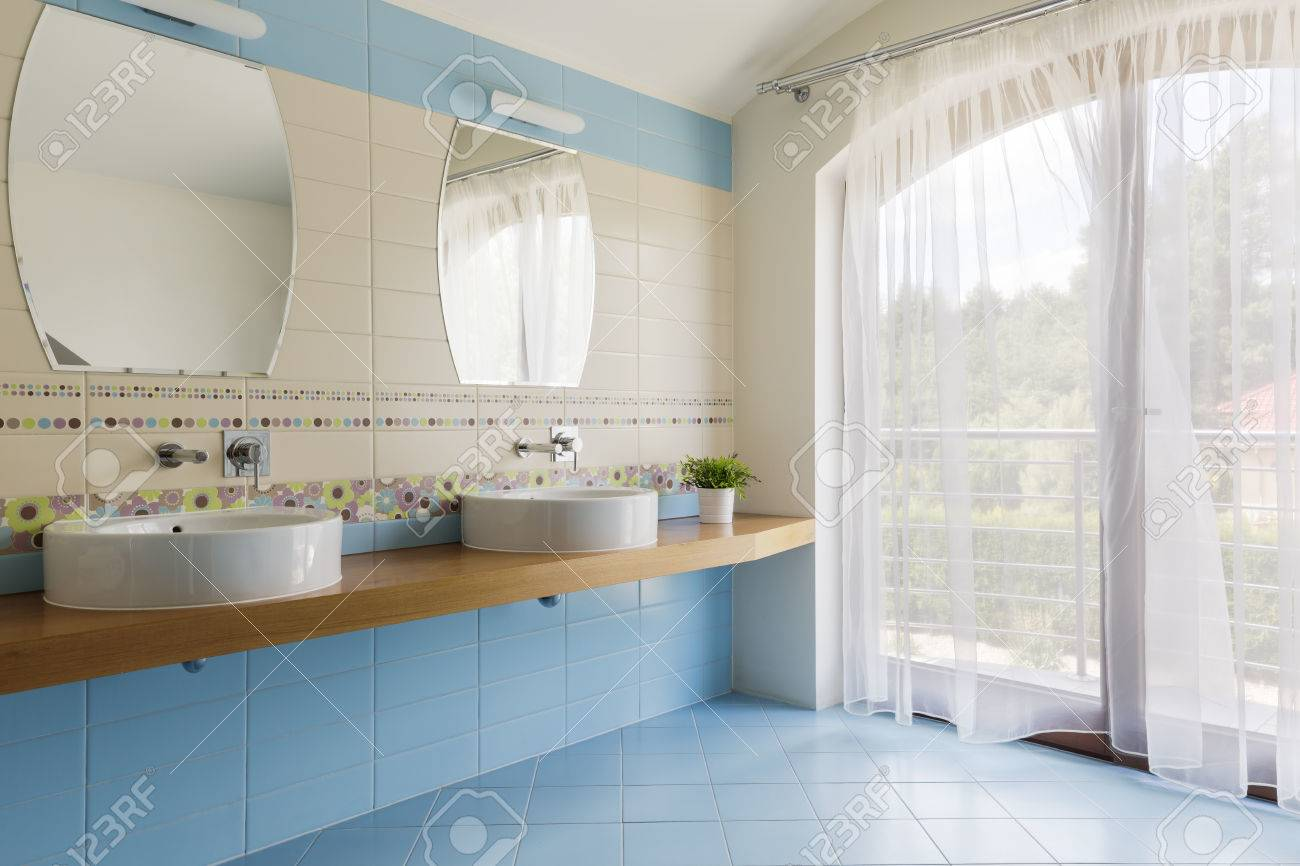 Spacious Bathroom With Blue And White Tiles, Two Countertop Basins ...
