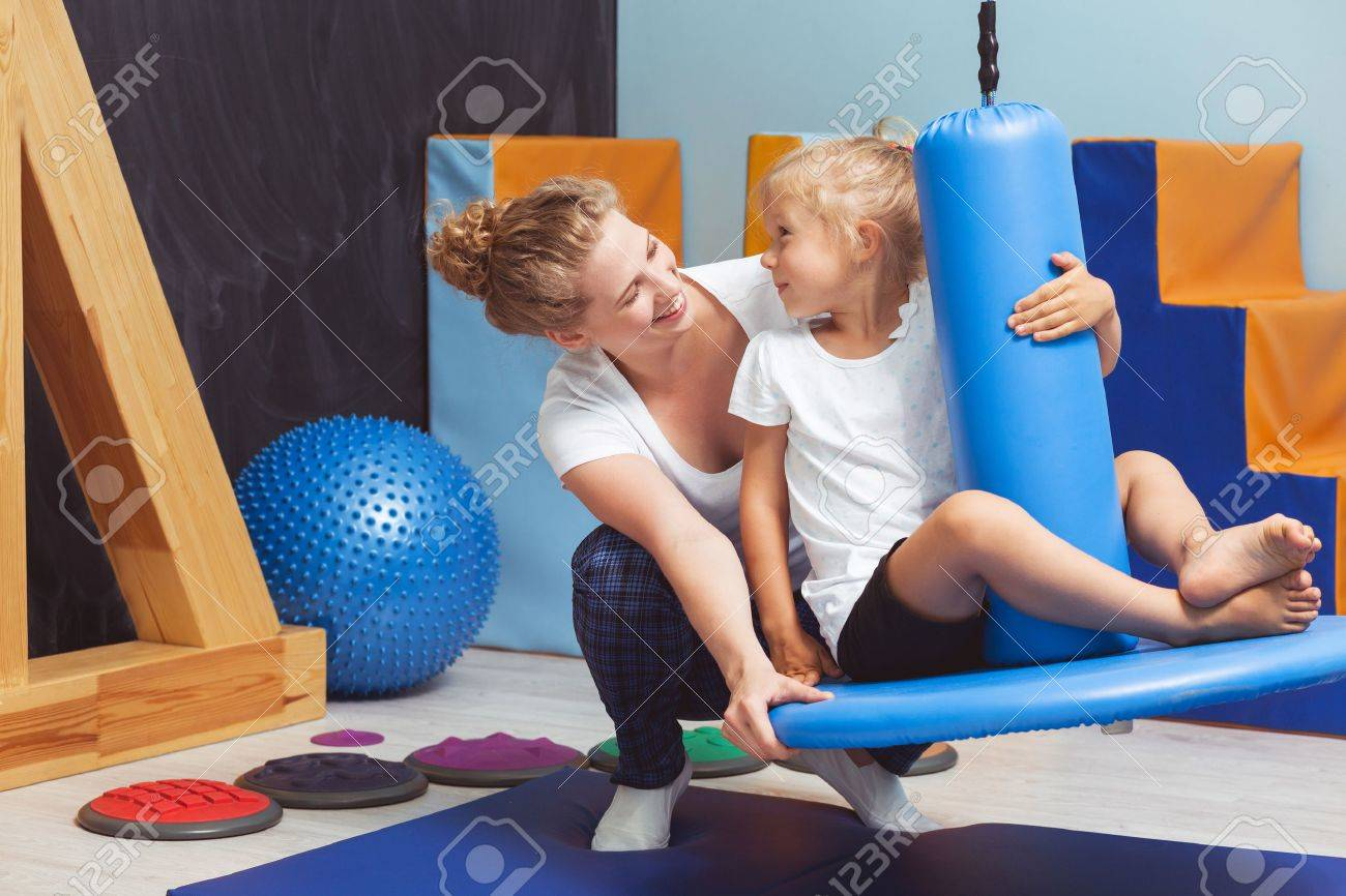 Young physiotherapist seesawing the girl on a blue swing Standard-Bild - 60772413