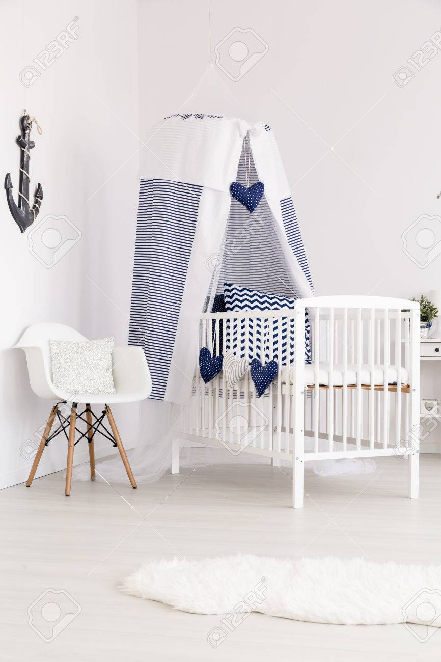 navy blue decorated canopy crib next to a white chair in the stock