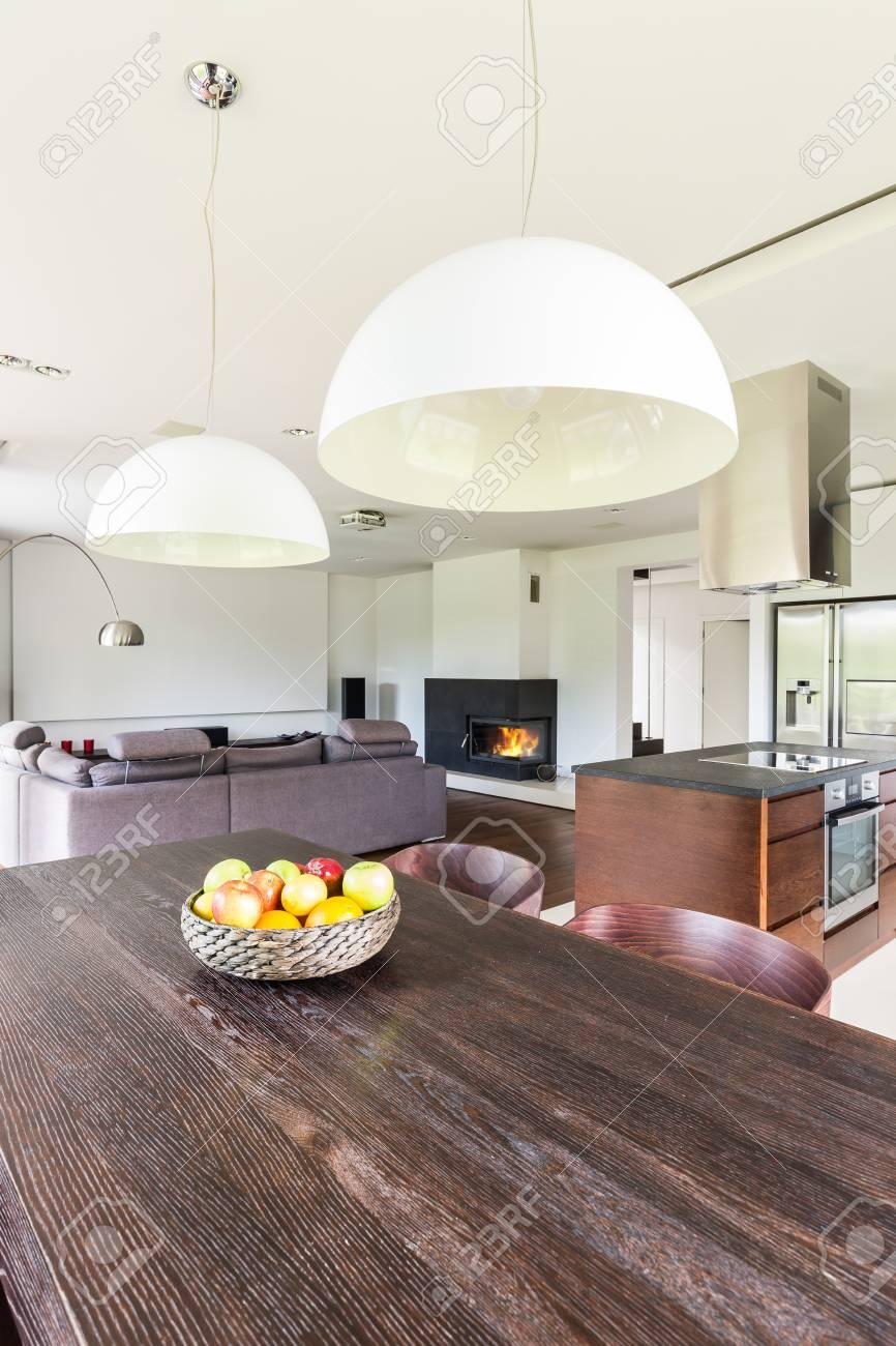 Piso abierto moderno con mesa de comedor de madera oscura y lámpara  colgante blanca