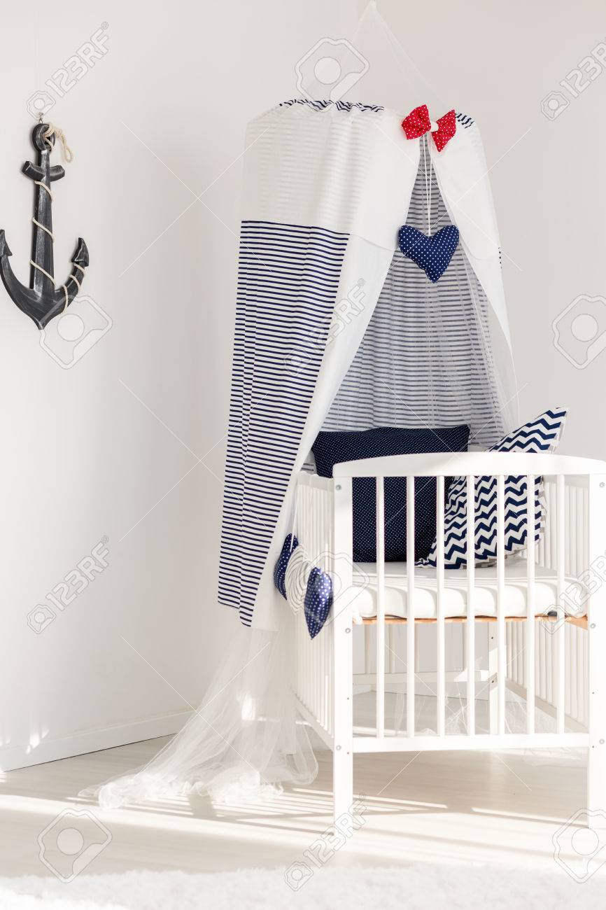 White canopy cot in marine style in a corner of a baby room illuminated with sunlight & White Canopy Cot In Marine Style In A Corner Of A Baby Room ...