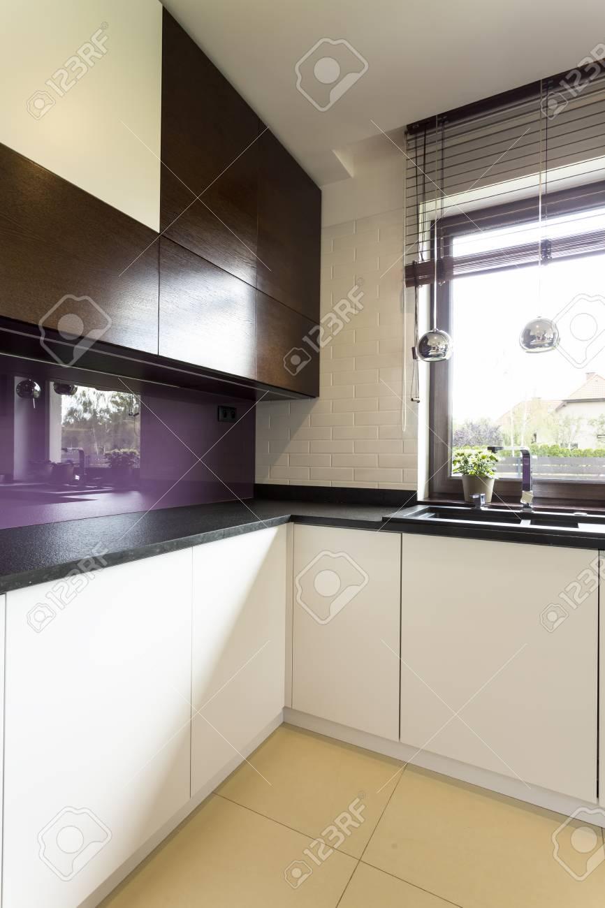 Idée de la cuisine légère avec placards blancs et noirs, plan de travail  sombre et dosseret violet