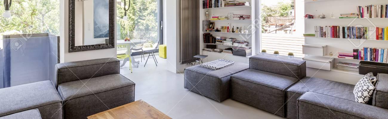 Soggiorno moderno con comodi sedili, librerie e grandi finestre, panorama