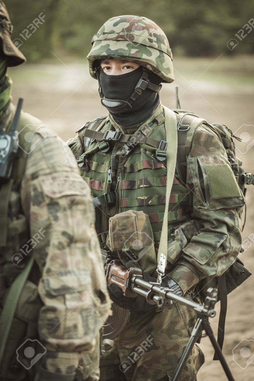c6b51694a379f Shot of a soldier in camouflage clothes and helmet with a weapon in his  hands Stock