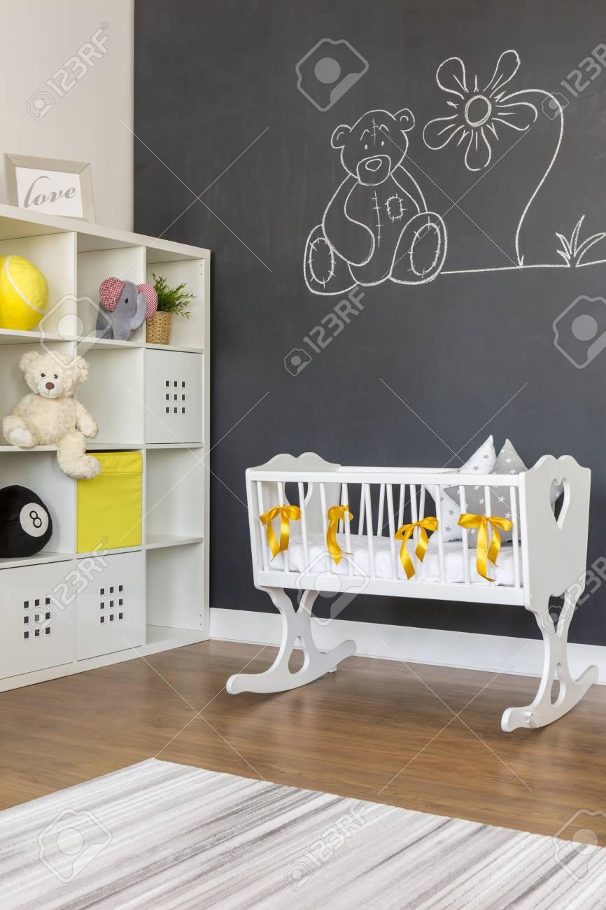 Blanc berceau de bébé avec bowknots jaune dans la chambre tableau noir